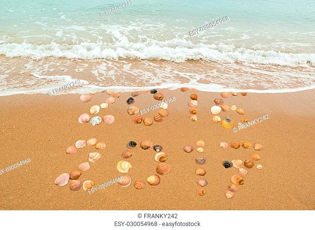 Happy New Year 2017 concept: The waves are about to cover and wash away 2016 whilst 2017 is still present, both years placed with seashells on the beach
