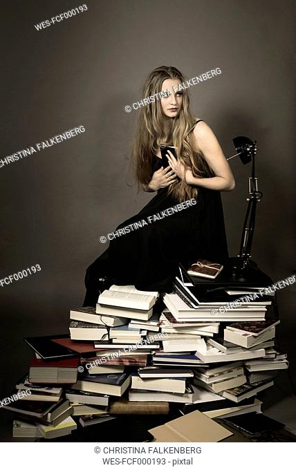 Portrait of young woman sitting with desk lamp on stack of books