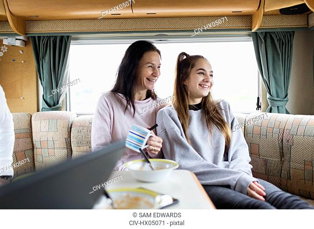 Happy mother and daughter enjoying breakfast in motor home