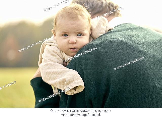 baby on shoulder of old man, generations, youth, at Neuhofener Berg, Munich, Germany