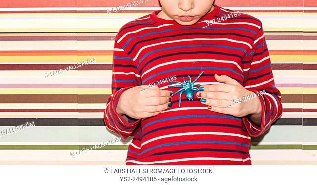Little girl holding a plastic toy spider in her hands. Conceptual image of childhood curiosity, fantasy and adventure