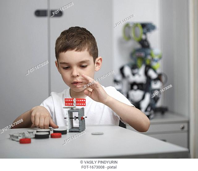 Cute boy operating machinery at table in classroom