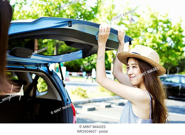 Smiling young woman with long brown hair, wearing Panama hat, closing the rear hatch of a car