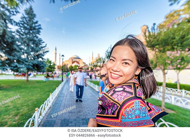 Beautiful woman takes selfie with view of Sultanahmet or Blue Mosque on background in Istanbul,Turkey