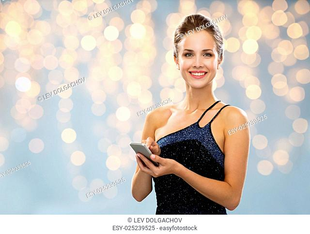 technology, smartphone, communication, people and holidays concept - smiling woman in evening dress holding smartphone over lights background
