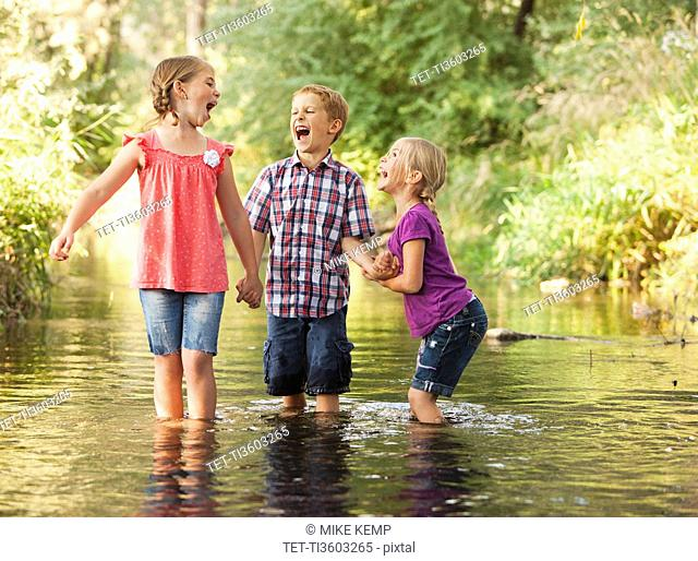 Three kids 4-5, 6-7 playing together in small stream