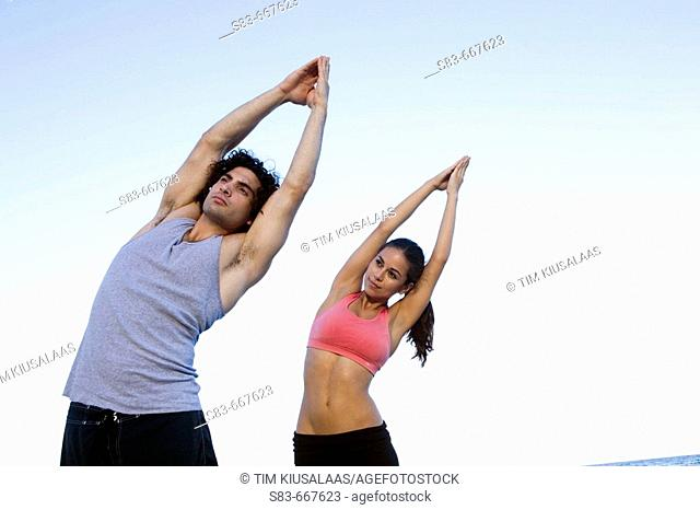 Young couple doing voga on the beach
