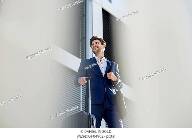 Smiling businessman with baggage in the city looking around