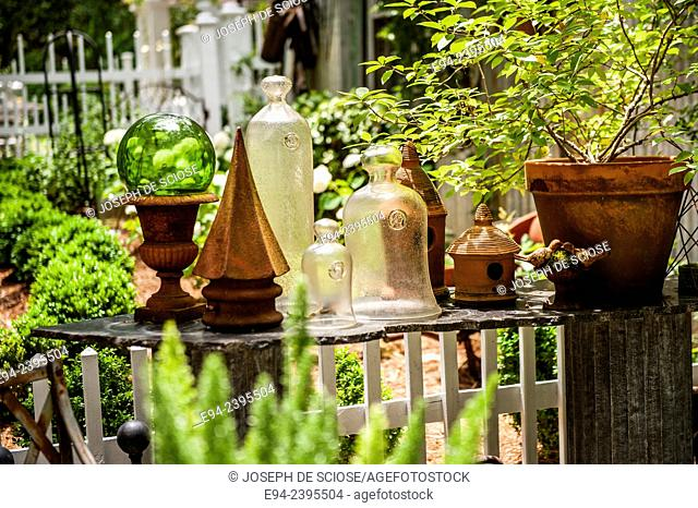 Table with terra-cotta pots and glass cloches in a garden setting.Georgia USA