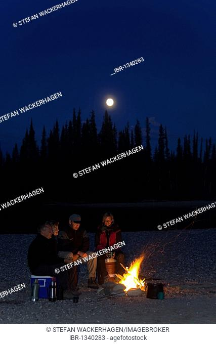 People sitting at a camp fire, bonfire, full moon behind, moonlight, shore of upper Liard River, Yukon Territory, Canada