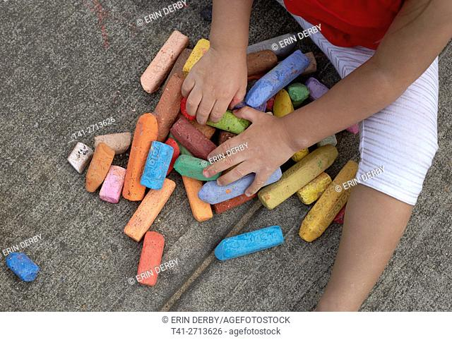 baby playing with chalk outside on concrete