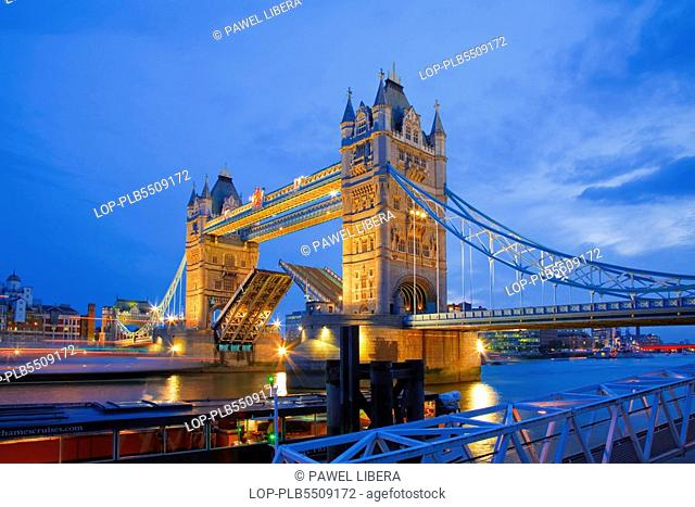 England, London, Tower Bridge, A boat passing under the raised bascules of Tower Bridge at Dusk