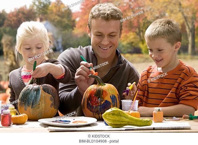 Caucasian father and children decorating pumpkins