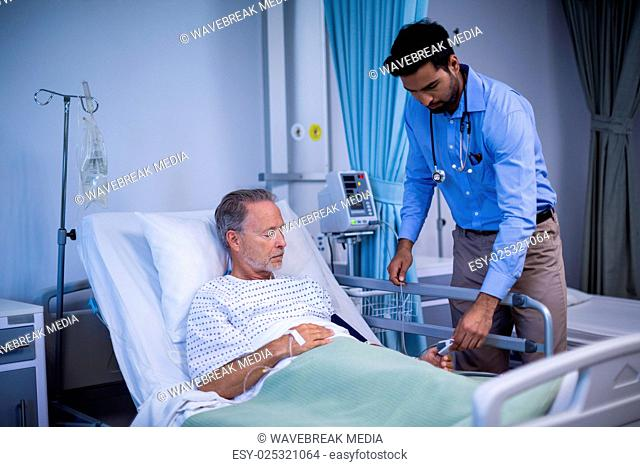 Doctor putting heart rate sensor on patients finger