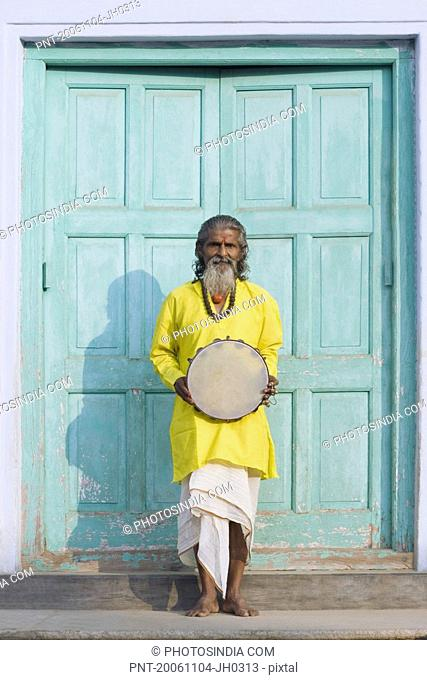 Senior man standing at the entrance of a house and holding a tambourine