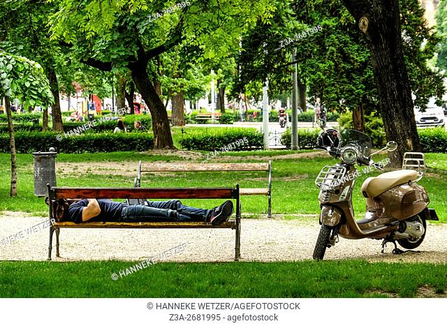 Man resting on a bench at Szabadság tér, Liberty Square in Budapest, Hungary