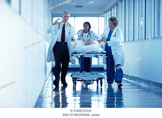 Doctors and a nurse pushing a patient through the hospital corridor on a gurney