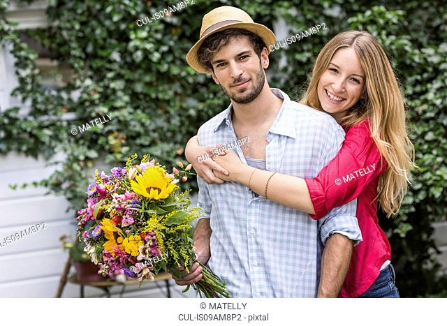 Portrait of young couple with bunch of flowers hugging in garden