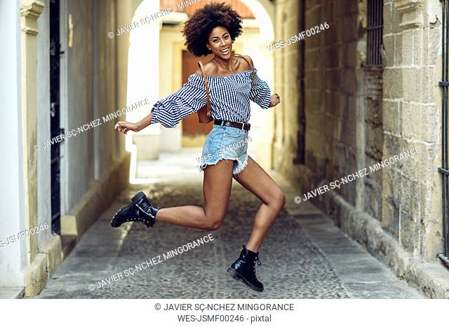 Portrait of laughing young woman jumping in the air