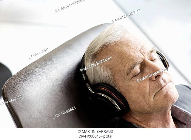 Senior man with headphones listening to music and reclining