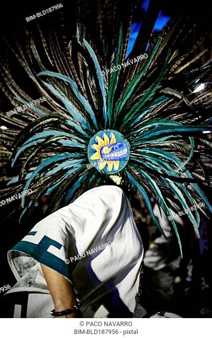 Dancer wearing feather headdress in performance