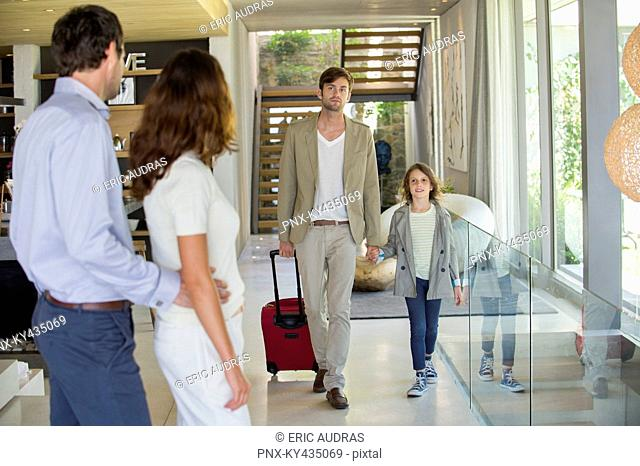 Man with his daughter arriving at his friends home from holiday