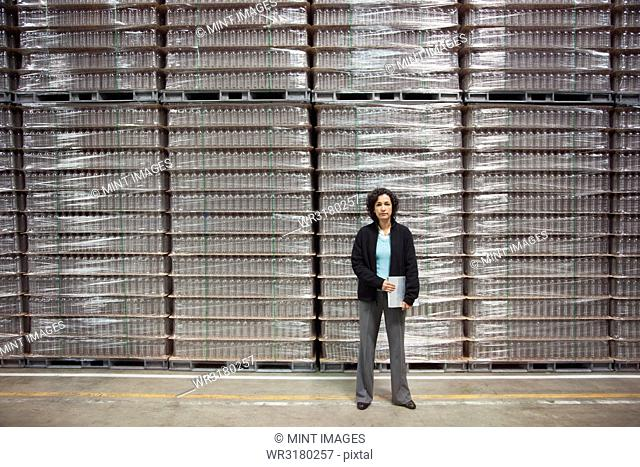 Portrait of an African American female manager in a storage warehouse for pallets of flavoured bottled water