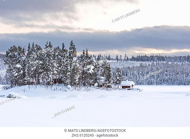 Winter landscape with old barns in forest with snowy spruce trees and small mountain in background, Jokkmokk county, Swedish Lapland, Sweden