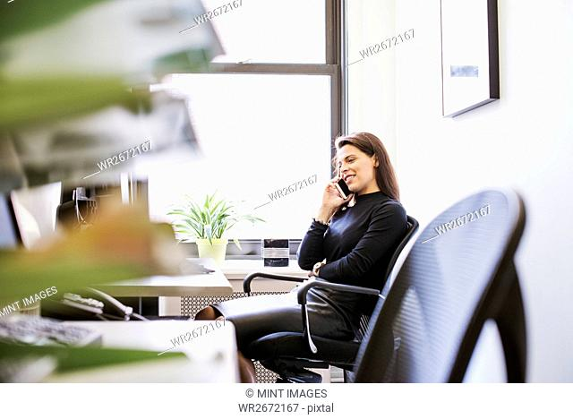 A young woman sitting at a desk with a cellphone to her ear