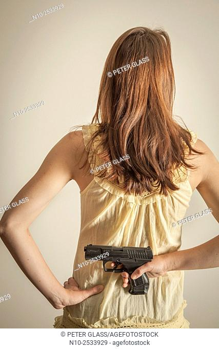 Young woman holding a gun behind her back