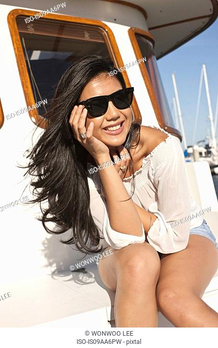 Portrait of young woman sitting on yacht, San Francisco, California, USA
