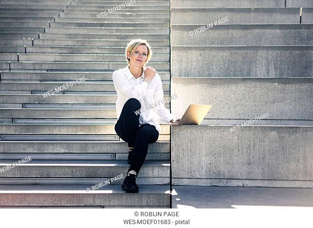 Young busineswoman sitting on stairs, using laptop