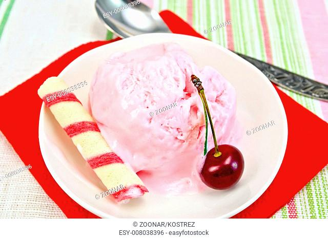Ice cream cherry on red paper napkin with spoon