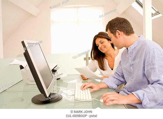 Mature couple checking bills and paperwork on home desktop computer
