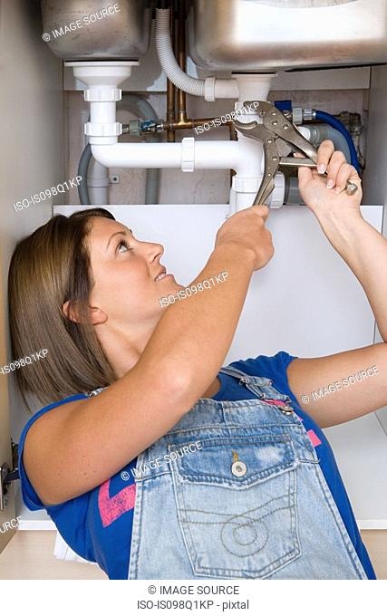 A young woman repairing a sink