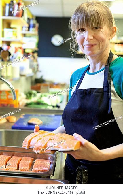 Woman holding raw salmon