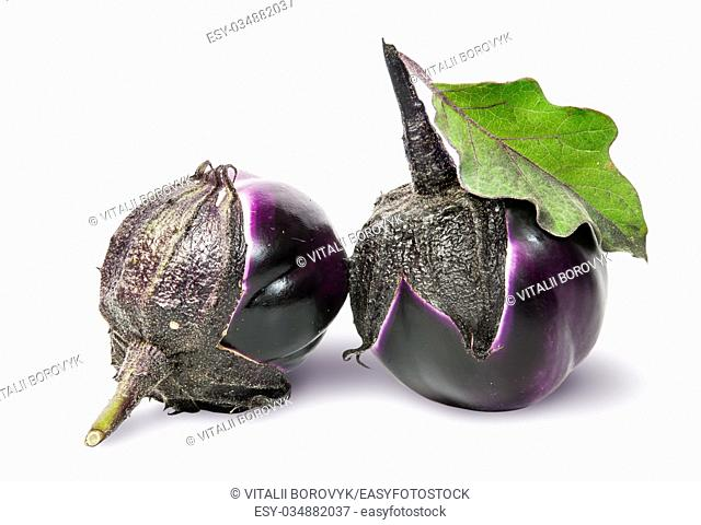 Two round ripe eggplant with green leaf rotated isolated on white background