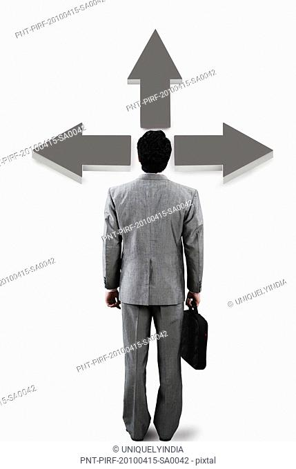 Businessman standing in front of a directional sign