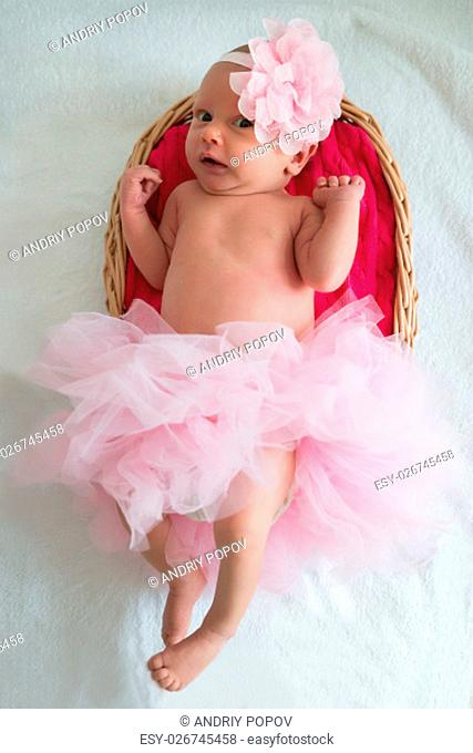 High Angle View Of A Baby Girl With Pink Tutu Lying In Wicker Basket