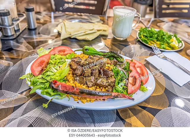 Close up detailed view of grilled delicious liver Turkish shish kebab served on a white plate with sliced lavash,parsley,onion,lettuce,tomatoes ,grilled pepper