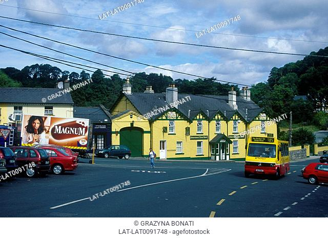 Town street. Bright yellow walls of Powerscourt Hotel. Bus,cars. Young woman