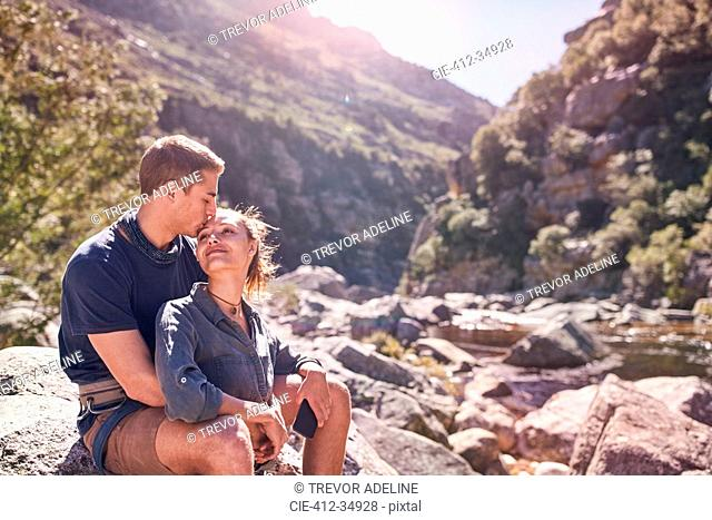 Affectionate young couple kissing at craggy, sunny stream