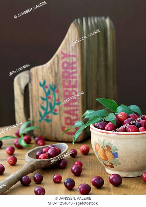 Fresh cranberries and a wooden cranberry scoop