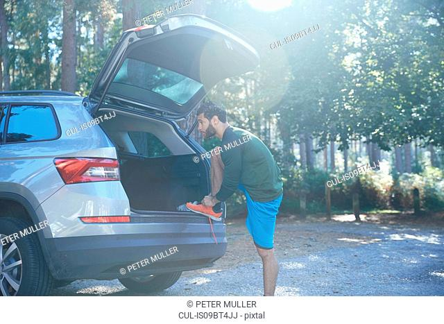 Male runner tying laces on car boot in sunlit forest