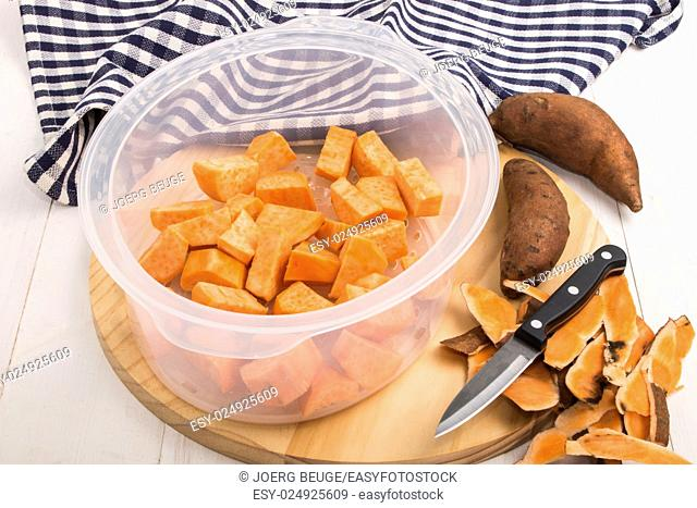 prepared potatoes in a food steamer insert, kitchen knife and peel