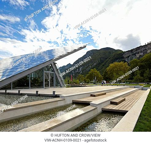 MUSE Science Museum, Trentino, Italy. Architect: Renzo Piano Building Workshop, 2013. Side view with ponds, timber decking and angular roof layers