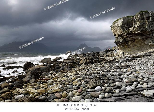 Tourists on rocks of Elgol beach at Port na Cullaidh with Red Cuillin Mountains under clouds on Loch Scavaig Isle of Skye Scotland UK