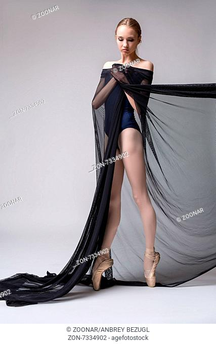Slim dancer plays with black mesh fabric in the studio