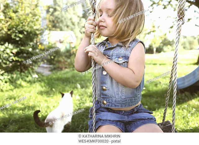Little girl sitting on swing in the garden
