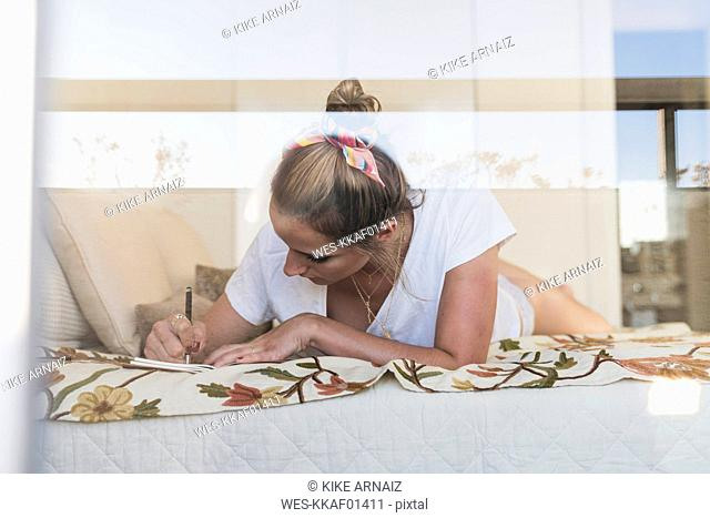 Young woman lying on bed at home writing in diary